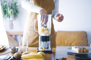 おうちカフェで、フルーツスムージーを作る女性の写真素材 [FYI04670482]