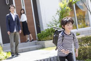 登校する小学生の男の子と見送る両親の写真素材 [FYI04670493]