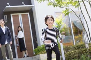 登校する小学生の男の子と見送る両親の写真素材 [FYI04670494]