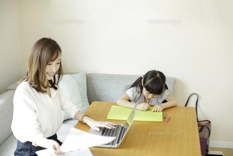 テレワークをする母親とお絵かきをする女の子の写真素材 [FYI04670505]