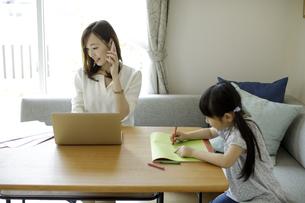 テレワークをする母親とお絵かきをする女の子の写真素材 [FYI04670506]