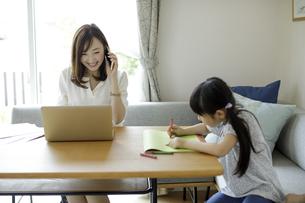 テレワークをする母親とお絵かきをする女の子の写真素材 [FYI04670507]