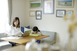 テレワークをする母親とお絵かきをする女の子の写真素材 [FYI04670508]