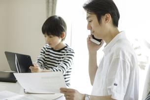 テレワークをする父親とタブレットPCを見る男の子の写真素材 [FYI04670511]