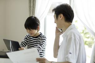 テレワークをする父親とタブレットPCを見る男の子の写真素材 [FYI04670512]