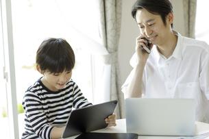 テレワークをする父親とタブレットPCを見る男の子の写真素材 [FYI04670515]