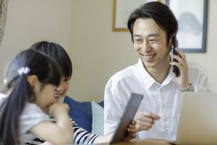 タブレットPCを見る子供たちとスマートフォンで話す父親の写真素材 [FYI04670518]