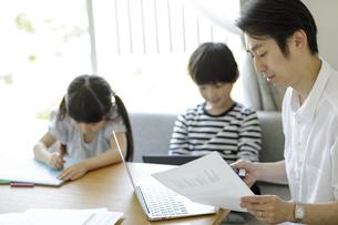 テレワークをする父親とそばで遊ぶ子供たちの写真素材 [FYI04670521]