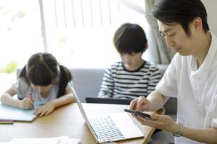 テレワークをする父親とそばで遊ぶ子供たちの写真素材 [FYI04670522]