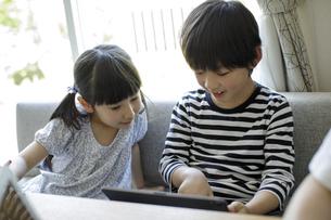 タブレットPCを見る男の子と女の子の写真素材 [FYI04670523]