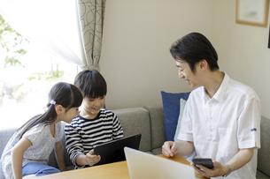 テレワークをする父親とタブレットPCを見る子供たちの写真素材 [FYI04670524]