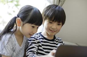 タブレットPCを見る男の子と女の子の写真素材 [FYI04670525]