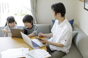テレワークをする父親とタブレットPCを見る子供たちの写真素材 [FYI04670527]