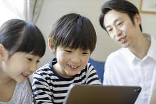 タブレットPCを見る子供たちと父親の写真素材 [FYI04670530]