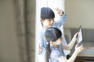 タブレットPCを見る男の子と女の子の写真素材 [FYI04670548]