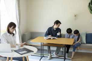 テレワークをする母親とリビングで過ごす家族の写真素材 [FYI04670549]