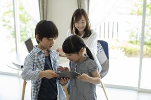 テレワークをする母親とタブレットPCを見る子供たちの写真素材 [FYI04670550]