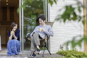 ウッドデッキでくつろぐ日本人夫婦の写真素材 [FYI04670562]