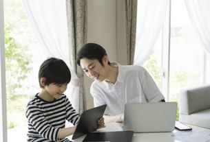 タブレットPCを見る男の子と父親の写真素材 [FYI04670582]