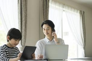タブレットPCを見る男の子とスマートフォンで話す父親の写真素材 [FYI04670583]
