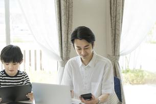 タブレットPCを見る男の子とスマートフォンを見る父親の写真素材 [FYI04670584]