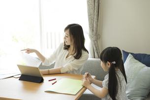 テレワークをする母親と女の子の写真素材 [FYI04670585]