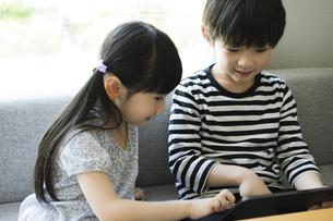 タブレットPCを見る男の子と女の子の写真素材 [FYI04670589]