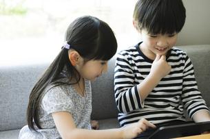 タブレットPCを見る男の子と女の子の写真素材 [FYI04670590]