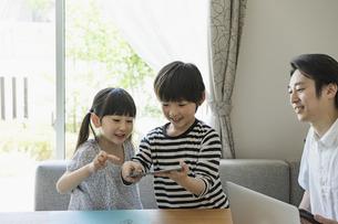 タブレットPCを見る子供たちと父親の写真素材 [FYI04670592]