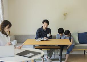 テレワークをする母親とリビングで過ごす家族の写真素材 [FYI04670595]