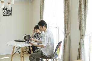 テレワークをする父親とタブレットPCを見る男の子の写真素材 [FYI04670604]