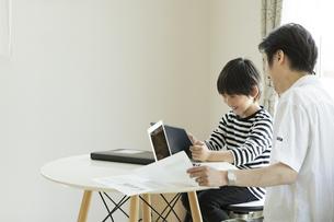 テレワークをする父親とタブレットPCを見る男の子の写真素材 [FYI04670606]