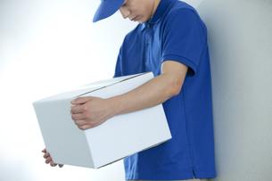 荷物を持つ配達員の男性の写真素材 [FYI04670686]