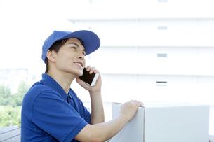 電話をする配達員の男性の写真素材 [FYI04670688]
