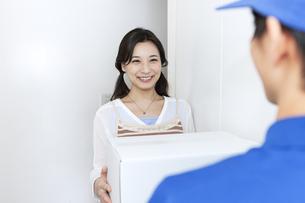 宅配物を受け取る女性の写真素材 [FYI04670715]
