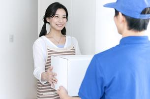 宅配物を受け取る女性の写真素材 [FYI04670720]