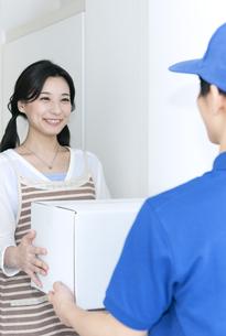 宅配物を受け取る女性の写真素材 [FYI04670721]