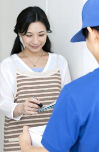受け取り荷物に印鑑を押す女性の写真素材 [FYI04670723]