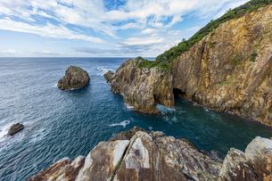 海面より鋭くそそり立つ花崗岩台地と海食洞の写真素材 [FYI04670993]