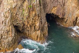 海面より鋭くそそり立つ花崗岩台地と海食洞の写真素材 [FYI04670996]