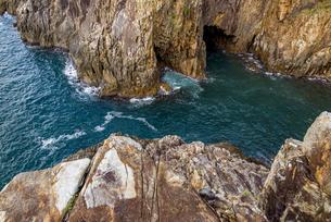 海面より鋭くそそり立つ花崗岩台地と海食洞の写真素材 [FYI04671000]