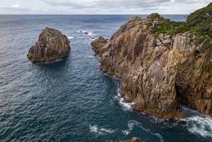 海面より鋭くそそり立つ花崗岩台地と海食洞の写真素材 [FYI04671002]