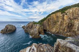 海面より鋭くそそり立つ花崗岩台地と海食洞の写真素材 [FYI04671003]
