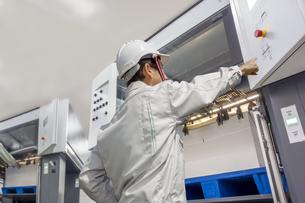 印刷工場で枚葉オフセット印刷機を操作する作業着を着た男性オペレーターの後ろ姿の上半身。の写真素材 [FYI04671059]