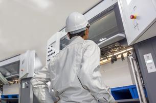 印刷工場で枚葉オフセット印刷機を操作する作業着を着た男性オペレーターの後ろ姿の上半身。の写真素材 [FYI04671060]