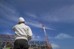 青空を背景にビル工事現場を見つめる作業着を着た男性技師の後ろ姿。の写真素材 [FYI04671061]