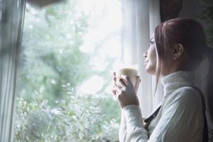 窓辺で手作りジュースのスムージーを飲む若い女性のイメージ写真の写真素材 [FYI04671215]