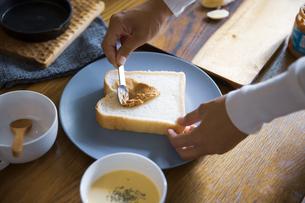 ピーナツバターとバナナの甘いスイーツトーストを料理する女性のイメージ写真の写真素材 [FYI04671217]