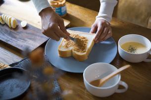ピーナツバターとバナナの甘いスイーツトーストを料理する女性のイメージ写真の写真素材 [FYI04671218]