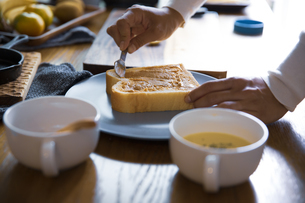 ピーナツバターとバナナの甘いスイーツトーストを料理する女性のイメージ写真の写真素材 [FYI04671219]